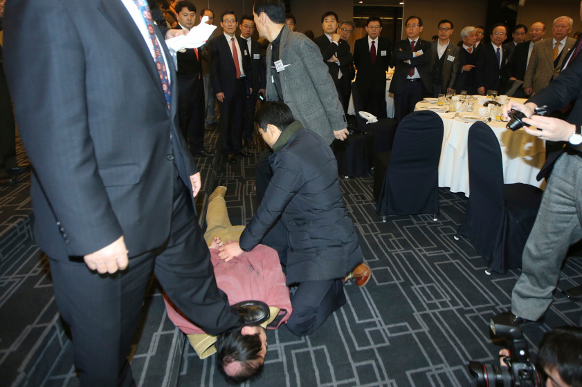 Security personnel detain an unidentified assailant who attacked the U.S. ambassador to South Korea Mark Lippert at a public forum, in central Seoul